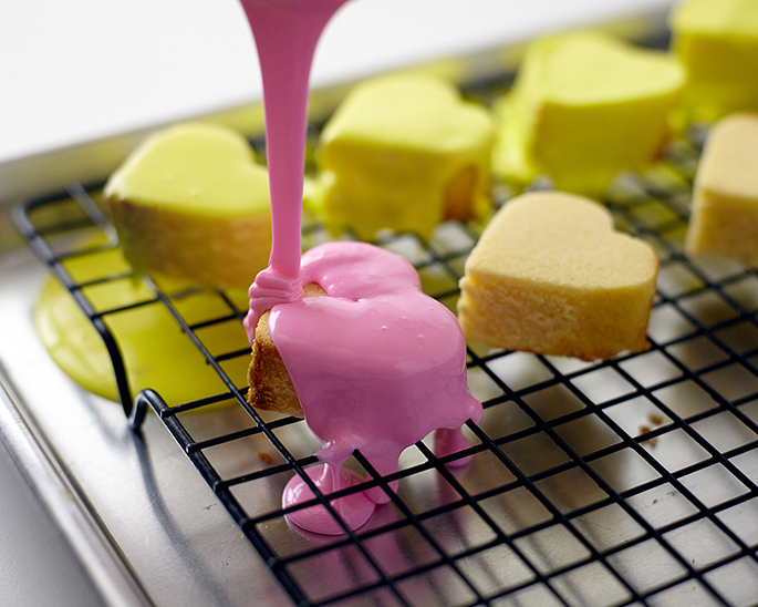Coat conversation hearts with tinted glaze.