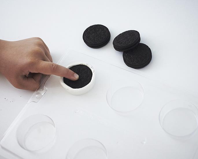 Pressing an Oreo into a cookie mold