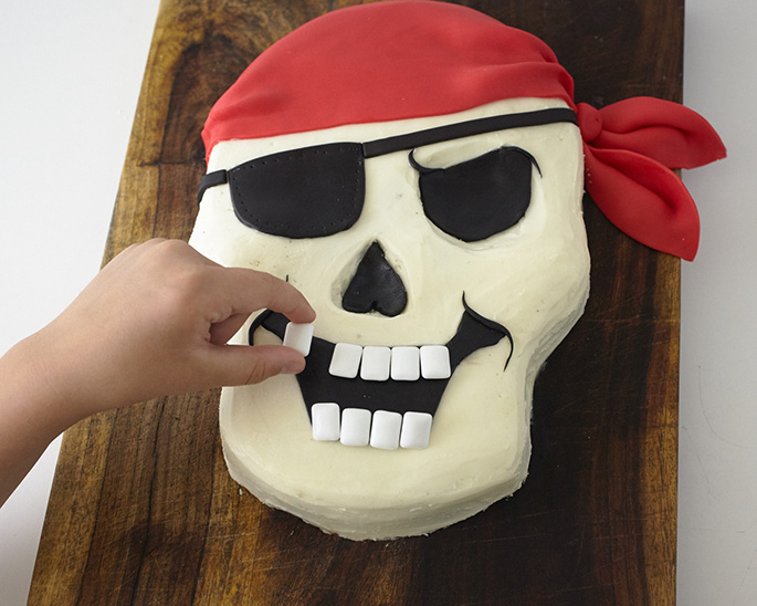 Adding gum teeth to a pirate skull cake