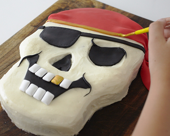 Painting a pirate skull party cake