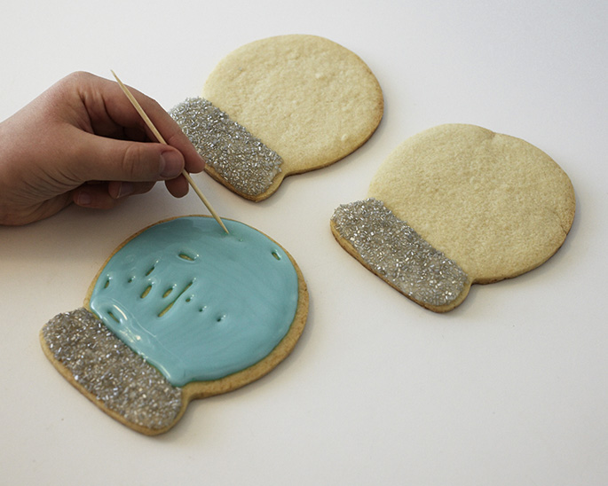 Filling in Snow Globe Sugar Cookie with glaze