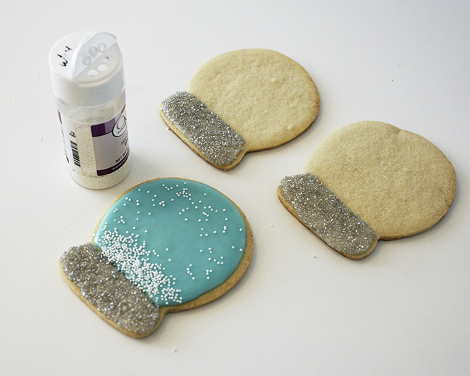 Adding edible confetti to snow globe sugar cookies