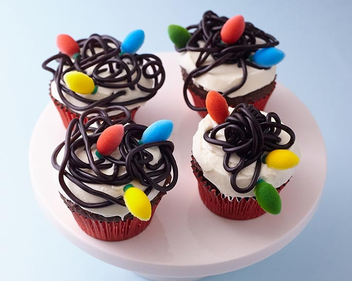 These cupcakes are quick and easy. String licorice and premade edible sugar Christmas lights will have these decorated in no time.
